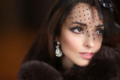 Beauty retro woman portrait in hat with lace. Elegant lady in  l. Uxury fur coat and fashion earrings. Winter Stock Photography