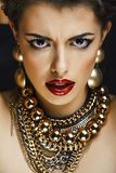 Beauty rich brunette woman with a lot of gold jewellery, hispani. C curly lady glamour on black background royalty free stock photography