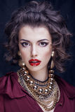 Beauty rich brunette woman with a lot of jewellery Royalty Free Stock Image
