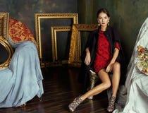 Beauty rich brunette woman in luxury interior near. Empty frames, vintage elegance royalty free stock photography