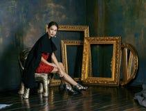 Beauty rich brunette woman in luxury interior near. Empty frames, vintage elegance brunette stock photography