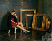 Beauty rich brunette woman in luxury interior near. Empty frames, vintage elegance stock photos