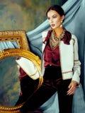 Beauty rich brunette woman in luxury interior near empty frames. Vintage elegance royalty free stock image