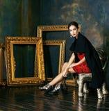 Beauty rich brunette woman in luxury interior near empty frames, vintage elegance. Brunette Royalty Free Stock Photo