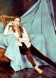 Beauty rich brunette woman in luxury interior near empty frames, vintage elegance. Brunette Royalty Free Stock Photos