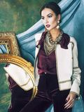 Beauty rich brunette woman in luxury interior near empty frames, vintage elegance brunette. Hispanic stock photo