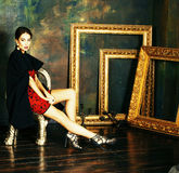 Beauty rich brunette woman in luxury interior near empty frames,. Vintage elegance, gold close up royalty free stock photo