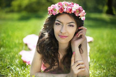 Beauty Romantic Girl Outdoors. Attractive teen with flowers on h. Ead lying on green grass field at park Royalty Free Stock Photos
