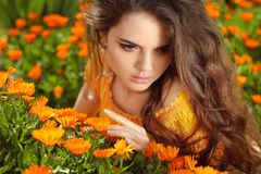 Beauty Romantic Girl Outdoors. Beautiful Teenage Model girl  pos. Ing over marigold flowers field. Enjoyment Stock Image
