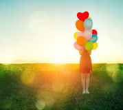 Beauty romantic girl on summer field with colorful air balloons royalty free stock photo