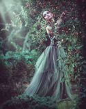Beauty romantic model girl fashion posing in garden trees, enjoying nature in apple orchard. Beautiful brunette young woma royalty free stock photo