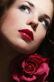 Beauty With Rose. Close-up portrait of beautiful woman with green eyes and large red pink rose. Delicate romantic beauty and fashion concept. Dark mysterious Stock Images
