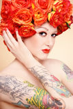 Beauty in roses. Beautiful glamorous girl with tattoos and fancy wig of bright orange roses stock photo