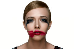 Beauty sad female Model with smeared Mascara and red Lipstick. Royalty Free Stock Images