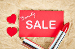 Beauty sale card with red lipstick. Beauty sale card with red lipstick on brown paper Stock Photography