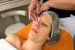 Beauty salon. A woman's face is cleaned with a wad of cotton wool in a beauty salon Royalty Free Stock Photography