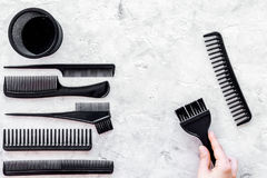 Beauty salon black work tools with comb for hair dress and coloring on stone background top view Stock Photo