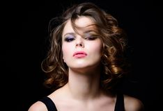 Beauty salon concept. Woman with curly hairstyle and makeup on black background. Makeup idea for elegant outfit. Professional makeup. Attractive elegant lady stock photography