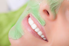 Beauty salon. Cosmetician applying facial mask at woman face. Stock Images