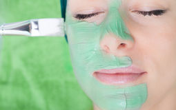 Beauty salon. Cosmetician applying facial mask at woman face. Beauty treatment concept. Woman relaxing in spa salon. Cosmetician applying clay facial mask at stock photography