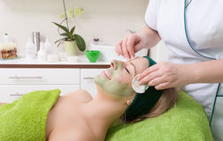 Beauty salon. Cosmetician removing facial mask from woman face. Beauty treatment concept. Woman relaxing in spa salon. Cosmetician removing clay facial mask royalty free stock image