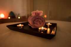 Beauty salon decoration in massage room, candles, towel and orch Royalty Free Stock Image