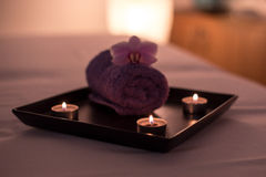 Beauty salon decoration in massage room, candles, towel and orchid Royalty Free Stock Photo