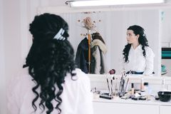 Beauty salon, girl with long black hair sits at the mirror in the beauty studio Stock Photos