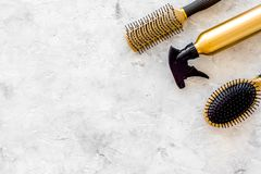 Beauty salon golden work tools with comb for hair dress and coloring on stone background top view mock up Royalty Free Stock Image