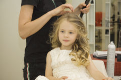 Beauty salon. Little girl with wet hair is being prepared to have her hair style Royalty Free Stock Photos