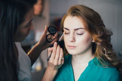 In the beauty salon. Make-up artist doing make-up, hairdresser doing hairstyle, beautiful models Stock Images