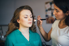 In the beauty salon. Make-up artist doing make-up, hairdresser doing hairstyle, beautiful models Stock Image