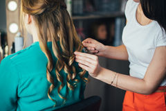 In the beauty salon. Make-up artist doing make-up, hairdresser doing hairstyle, beautiful models Royalty Free Stock Photo