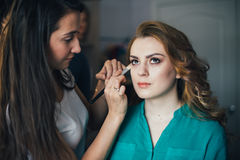 In the beauty salon. Make-up artist doing make-up, hairdresser doing hairstyle, beautiful models Royalty Free Stock Images