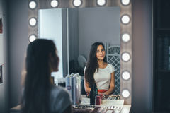 In the beauty salon. Make-up artist doing make-up, hairdresser doing hairstyle, beautiful models Stock Photos