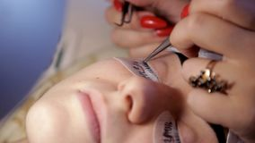 In the beauty salon, the make-up artist prepares the girl for the procedure of eyelash extension. Close-up stock footage