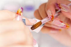 Beauty salon: Manicure, painting on nail. Manicurist treating client at beauty salon. Manicure stage: painting on nail Stock Images