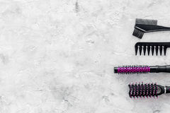 Beauty salon pink work tools with comb for hair dress and coloring on stone background top view mock up Royalty Free Stock Photo