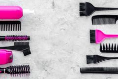 Beauty salon pink work tools with comb for hair dress and coloring on stone background top view mock up Royalty Free Stock Photography