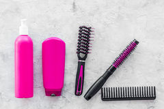 Beauty salon pink work tools with comb for hair dress and coloring on stone background top view mock up Royalty Free Stock Image