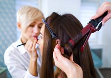 Beauty salon specialists doing professional makeup and hairstyle using curling iron for young woman stock photography