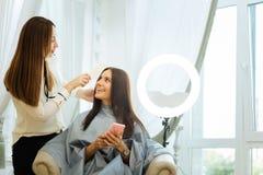 Positive joyful woman looking at her hair stylist. Beauty salon visitor. Positive joyful women smiling while looking at her hair stylist royalty free stock photo