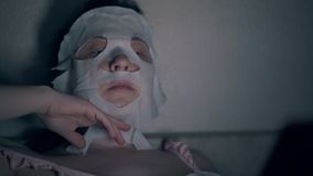 Beauty salon visitor in white regenerating sheet mask close. Beauty salon visitor in white regenerating sheet mask types on black smartphone in dark room close stock video