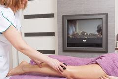 Beauty salon. Woman getting spa hot stone legs massage Stock Photos