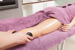 Beauty salon. Woman getting spa hot stone legs massage Royalty Free Stock Photography