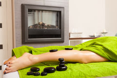 Beauty salon. Woman getting spa hot stone legs massage Stock Images