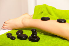 Beauty salon. Woman getting spa hot stone legs massage Stock Photography