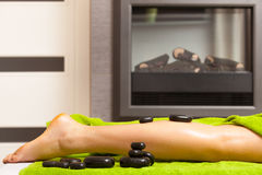 Beauty salon. Woman getting spa hot stone legs massage Royalty Free Stock Images