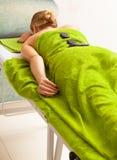 Beauty salon. Woman getting spa hot stone therapy massage Stock Photo