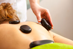 Beauty salon. Woman getting spa hot stone therapy massage Stock Images